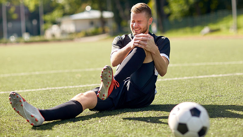 Male soccer player in pain with knee injury