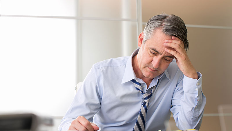 Man stressed at work in need of chiropractic care for stress relief