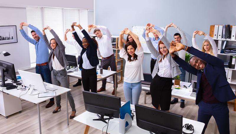 An office team stretching in office together