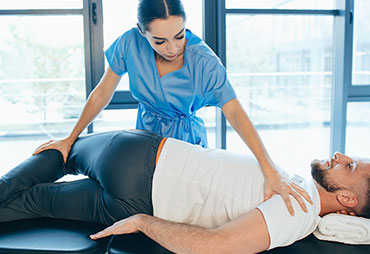 Male patient reciving chiropractic adjustment to relief sciatica